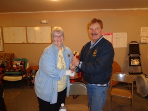 DG Lion Katherine Tweed (left) passes the gavel to incoming DGE Dwaine Heinrich.