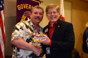 ID Robert receives prize from convention chair PDG Dan Mayer.